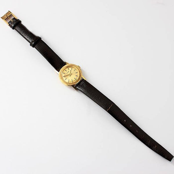 a gold cased ladies CYMA wrist watch with a black leather strap and plain batons