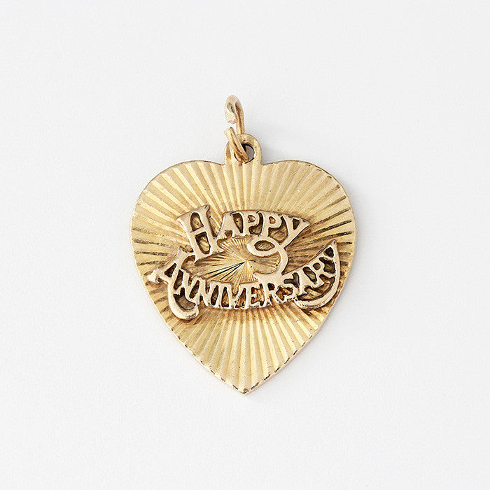a secondhand 9ct yellow gold heart shaped charm with happy anniversary written on it