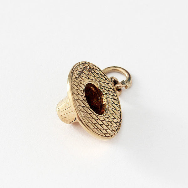 a plain yellow gold hat charm with a woven pattern on the top and a hallmark