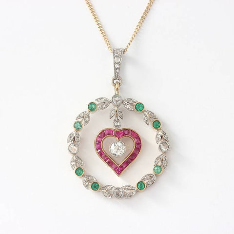 ruby heart shaped pendant with a central diamond and a surround of emeralds and diamonds in 18ct yellow gold pendant and curb link chain