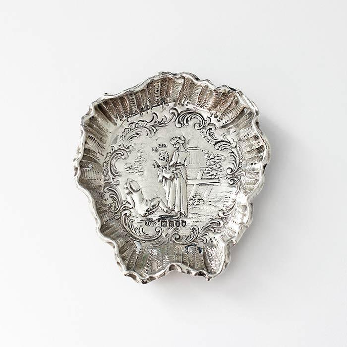 a small silver dish or tray with a pretty scene with a lady and flowers london import mark 1896