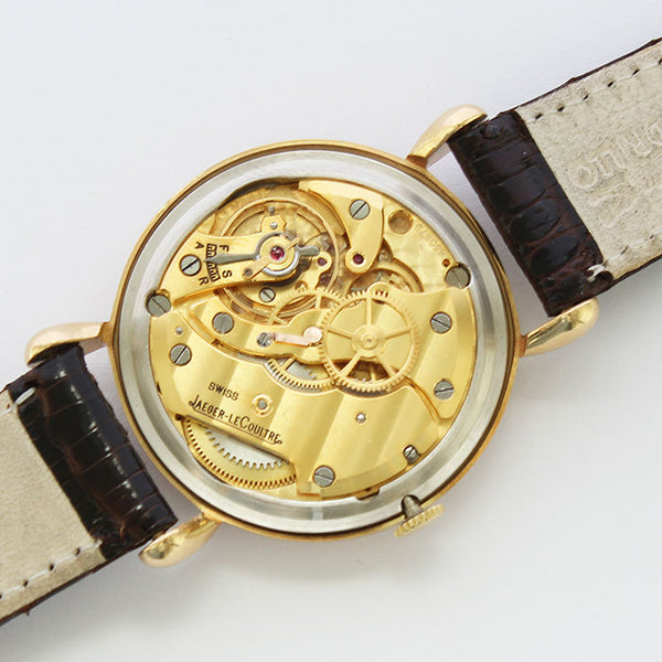 a vintage jaeger le coultre watch with 18 carat gold case and leather strap