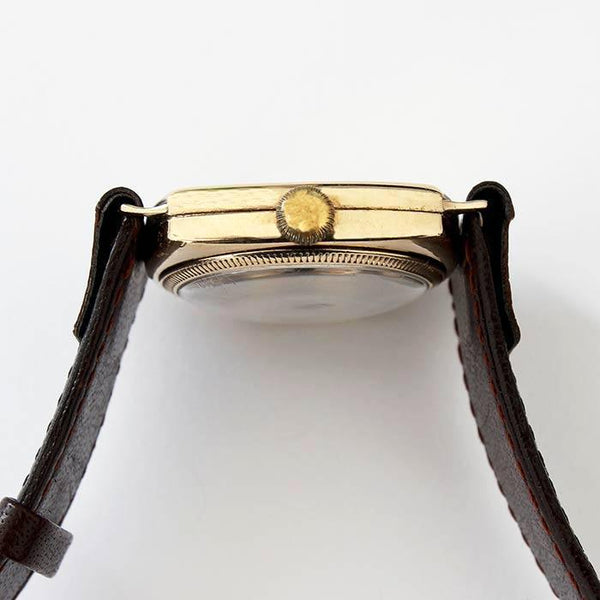 a vintage j w benson wrist watch with gold cushion case with modern leather strap