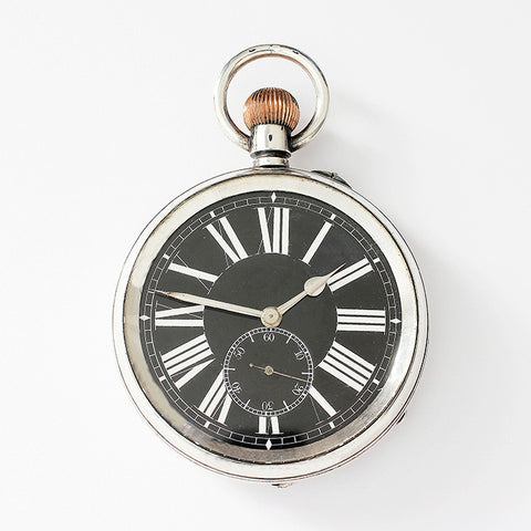 a large silver vintage pocket watch with engraving on the inside
