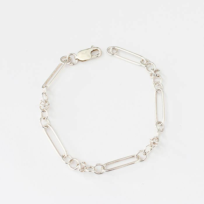 a sterling silver modern bracelet with rectangular open work links and circular open links in between with a strong clasp