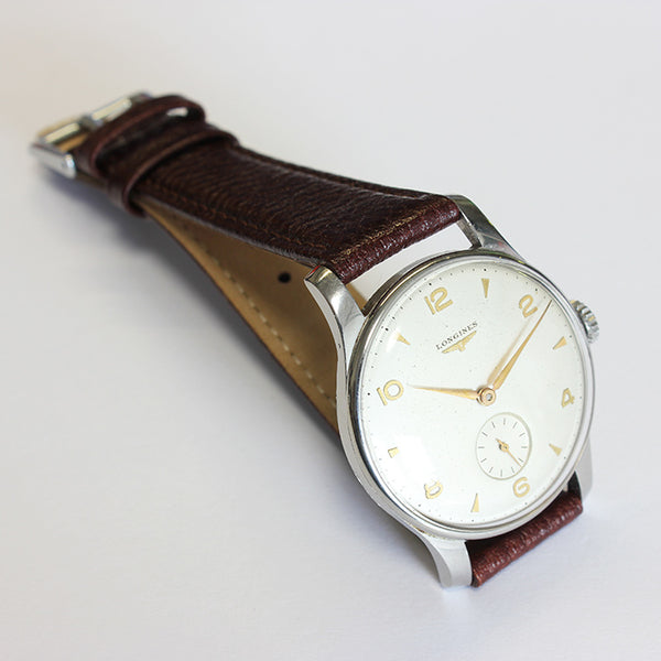 a mens vintage longings watch with a stainless steel case and champagne dial and brown leather strap