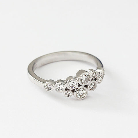 a modern diamond 10 stone ring in a rubover setting and in white gold