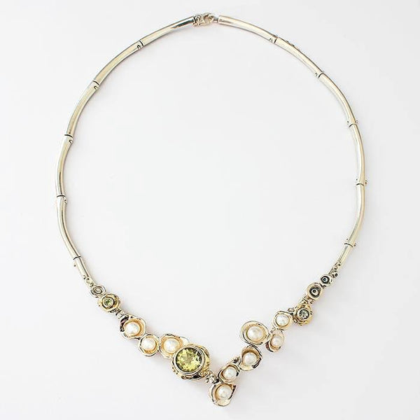 3 circular peridot stones with various pearls in a collar necklace with an abstract setting all in silver