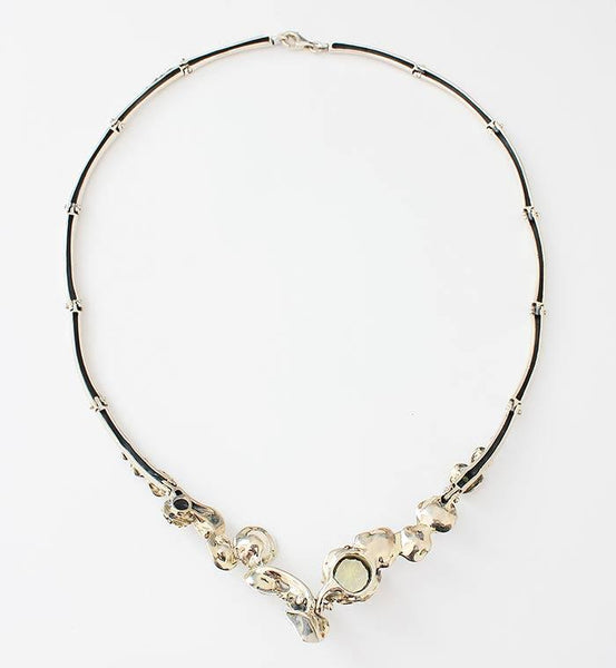 a modern sterling silver collar necklace with 3 round peridot stones and 9 various pearls in an abstract setting