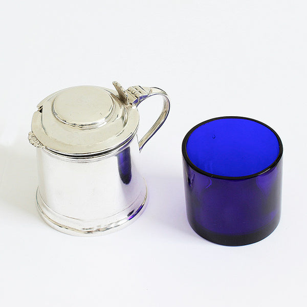 an antique solid silver mustard pot with plain handle and blue liner dated 1927