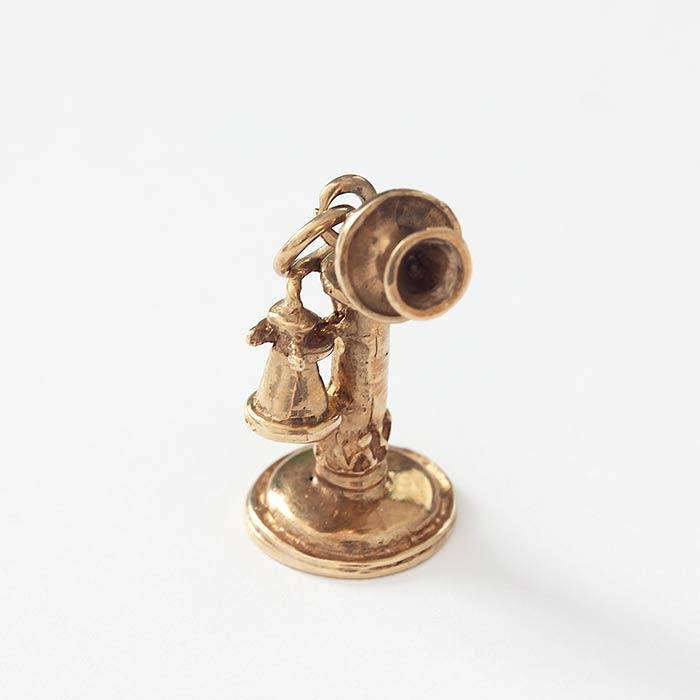 a vintage old fashioned telephone charm in yellow gold