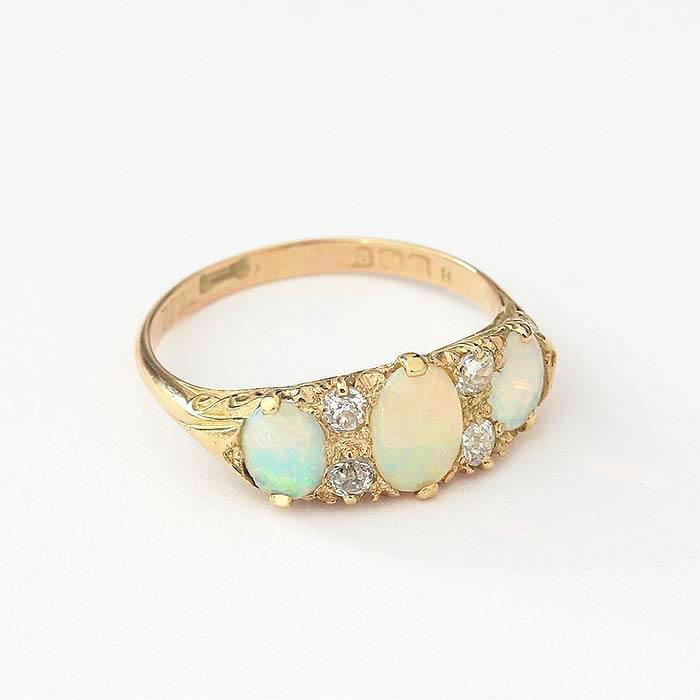 an vintage opal and diamond set ring with 4 diamonds and 3 oval opals in yellow gold