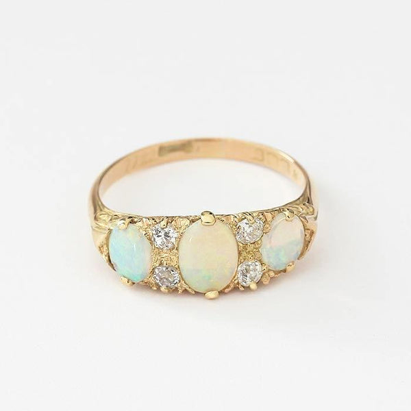 an opal and diamond set vintage yellow gold ring with scroll shoulders