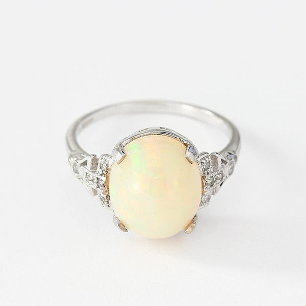 white gold opal and diamond ring with a claw setting and diamond shoulders