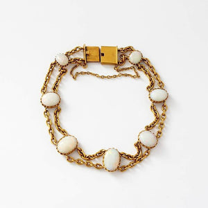 a beautiful oval opal yellow gold bracelet with 7 cabochon opals and a chain link in 18 carat gold