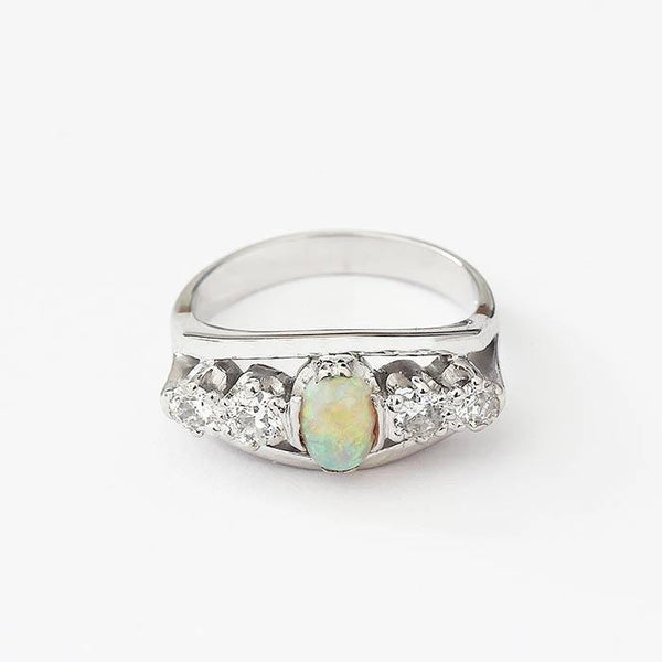 a preowned white gold central opal and diamond set band with claw setting