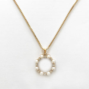a yellow gold circle pendant with 8 cultured pearls and 8 round diamonds on a box chain