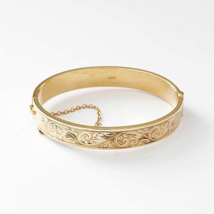 a yellow gold secondhand vintage part patterned engraved bangle with safety chain and box snap