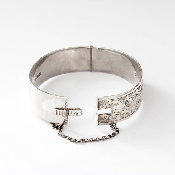 a vintage sterling silver part patterned oval hinged bangle with a safety chain