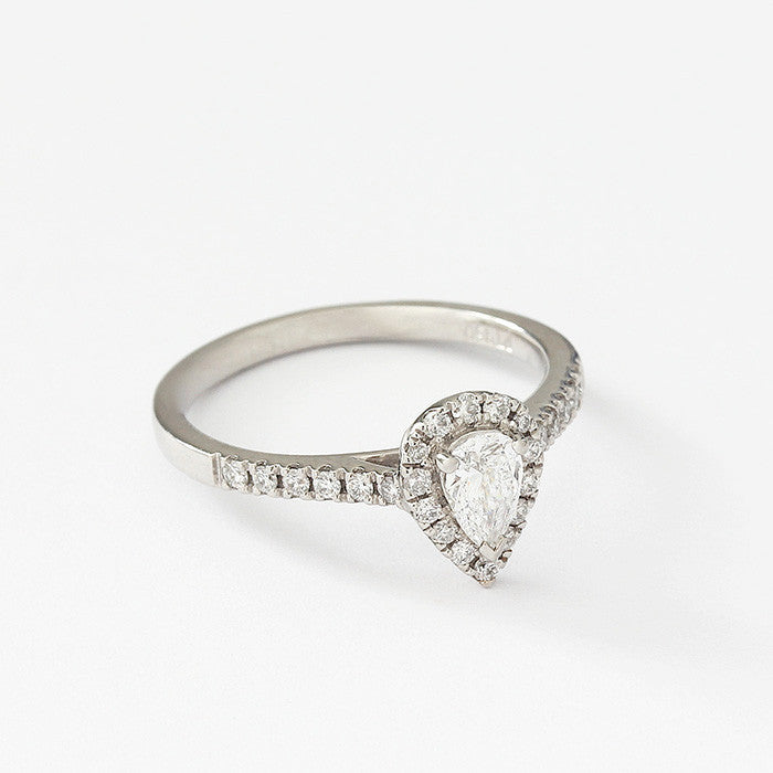 a platinum diamond cluster ring in a claw setting pear shaped centre stone