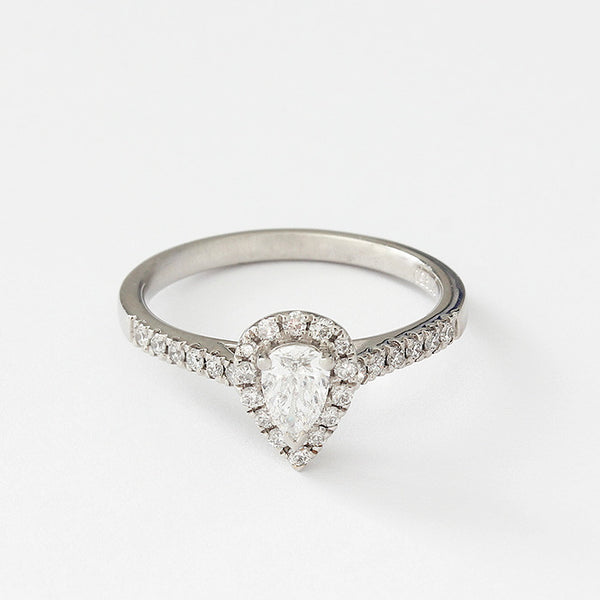 a diamond set cluster ring with a central pear shaped stone and small diamonds around head and shoulders