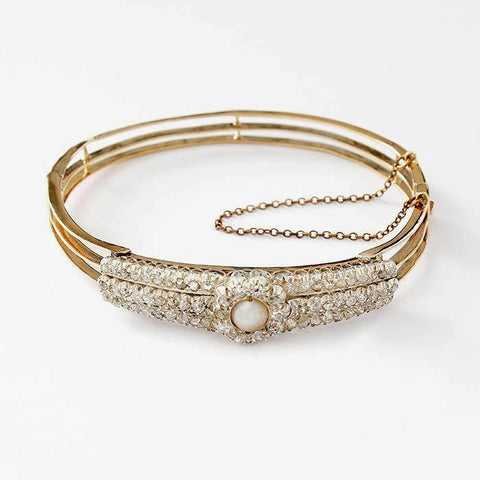 a pearl and diamond set cluster bangle in yellow gold with a safety chain