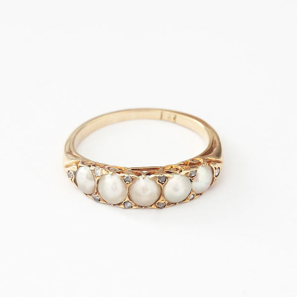 pearl and diamond half hoop ring with carved head and made in yellow gold