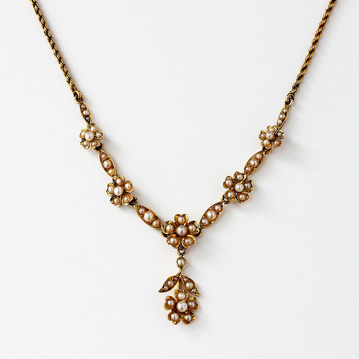 a vintage yellow gold flower and leaf design necklace with graduated pearls