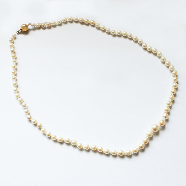 a preowned string of pearls with a plain polished gold ball clasp