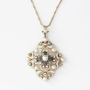 an antique pearl and diamond pendant with enamel and a floral pattern with slim gold chain