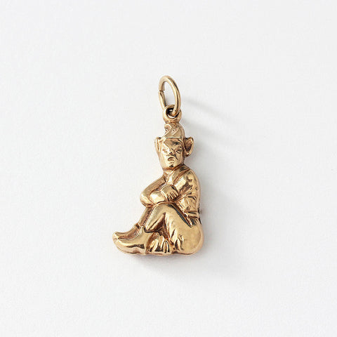 a 9ct yellow gold secondhand pixie charm which is sitting down