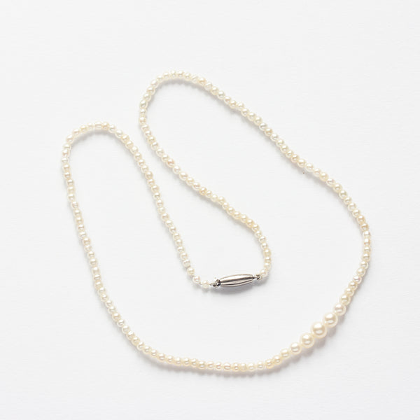 an antique plain natural pearl necklace with a white metal clasp
