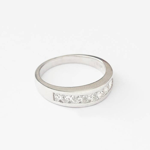a white gold half eternity ring with 7 uniform princess cut diamonds in a channel setting