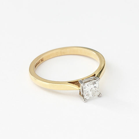 a diamond set single stone engagement ring in yellow and white gold with princess cut