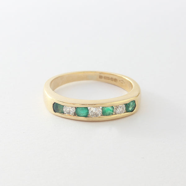a yellow gold half eternity ring with emeralds and diamonds