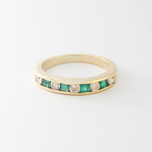 a diamond and emerald half eternity ring channel set in yellow gold metal