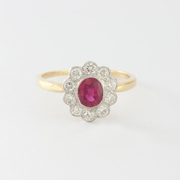 a cluster ring yellow and white gold central oval ruby and diamond surround