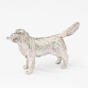 a solid silver retriever dog figure with a branch all british made