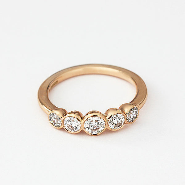 a modern rose gold diamond 5 stone ring with graduated stones