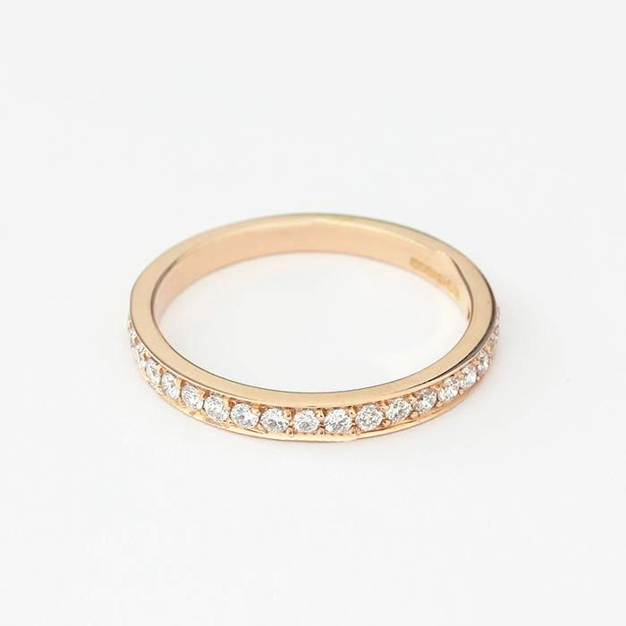 a rose gold three quarter eternity ring with diamonds in a grain setting and finger size M