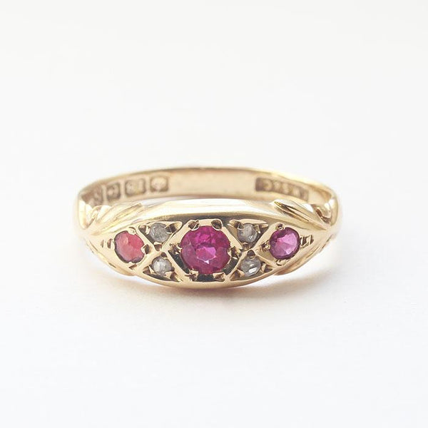 a secondhand ruby and diamond yellow gold ring with carved shoulders