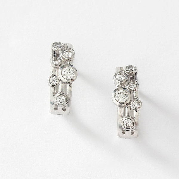 a diamond set of hoop earrings with rub-over settings 6 stones in each 18ct white gold
