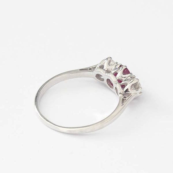 a white gold 3 stone ring with claw settings with a central round ruby and one round diamond either side
