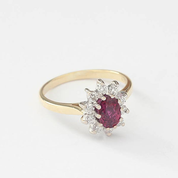 a beautiful ruby and diamond classic cluster ring with white gold settings and a yellow gold band