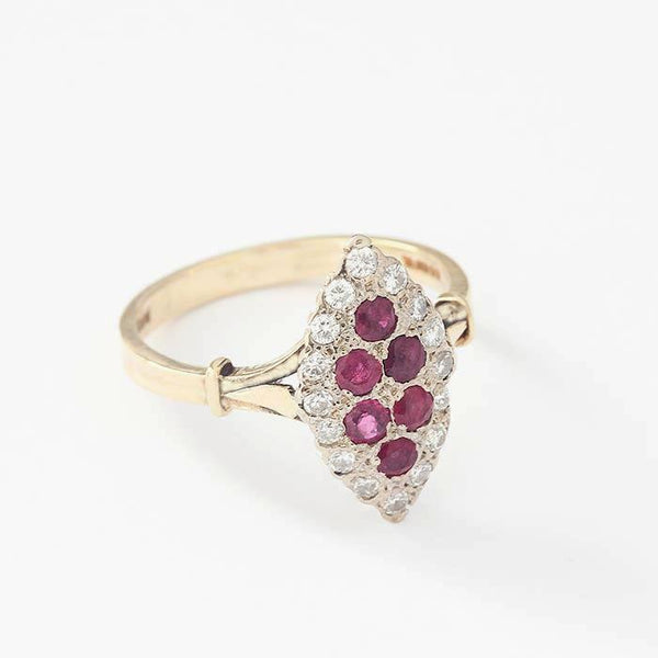 a marquise shaped vintage gold ring with 6 diagonal round rubies and a diamond surround