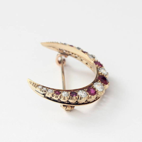 a ruby and diamond crescent shaped brooch with yellow gold settings and bar