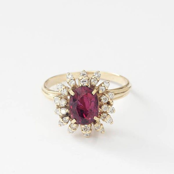 a beautiful ruby and diamond oval cluster ring in a claw setting in yellow gold