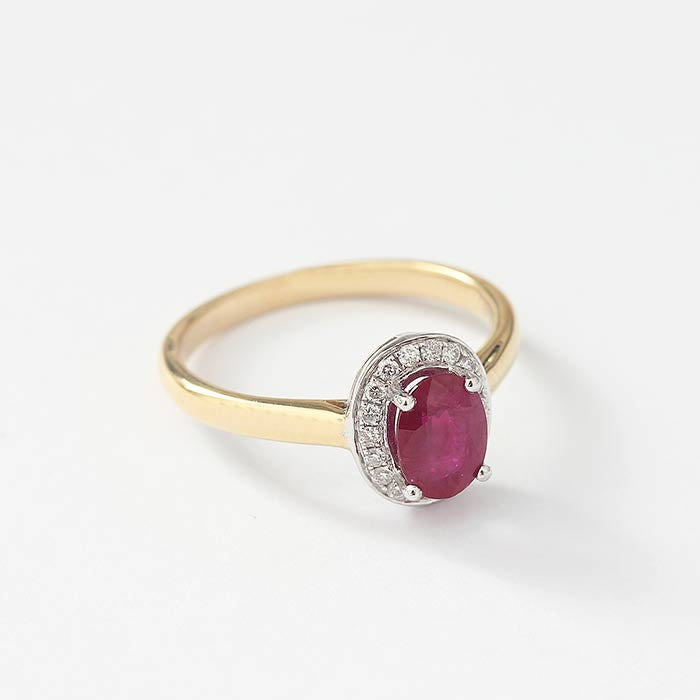 a vintage oval central ruby with a surround of diamonds in a  cluster setting in a yellow gold band