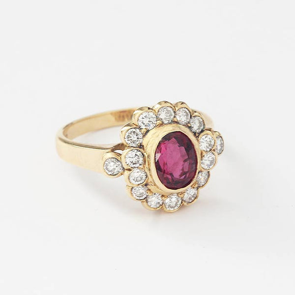 an oval central ruby and a surround of 14 diamonds in a rub-over setting with a yellow gold plain band