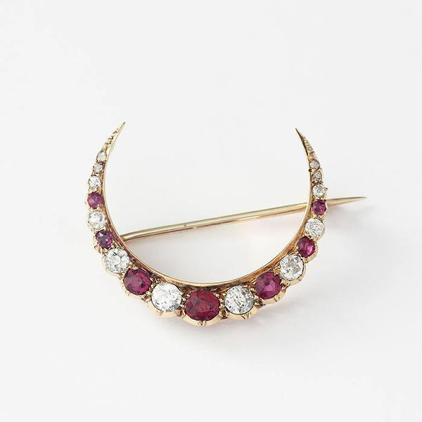 an antique ruby and diamond crescent shaped graduated brooch in yellow gold